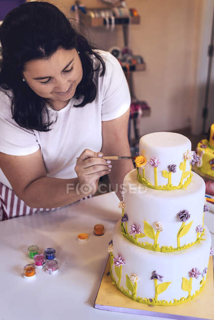 Confectioner decorating layered cake with flowers — Stock Photo