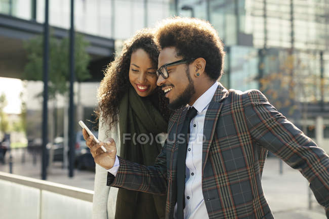 Two smiling young business people sharing smartphone in front of office building — Stock Photo
