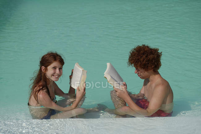 Redheaded girl and boy sitting at  pool edge reading a book — Stock Photo
