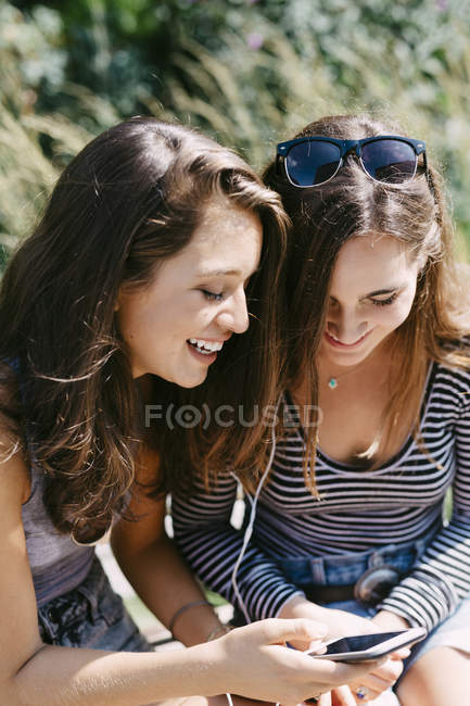 Two happy friends listening music with earphones — Stock Photo