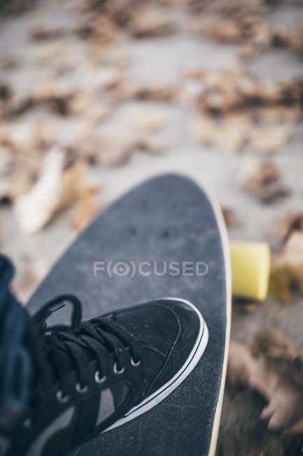 Männliche schwarze Sneaker auf longboard — Stockfoto