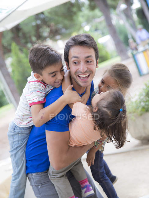Joven jugando con tres niños - foto de stock