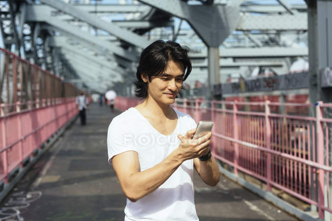 USA, New York City, man on Williamsburg Bridge in Brooklyn checking the cell phone — Stock Photo