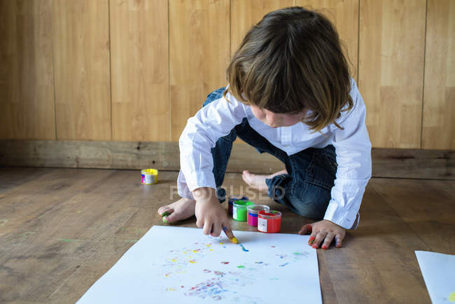 Little boy crouching on wooden floor painting with finger colours — Stock Photo