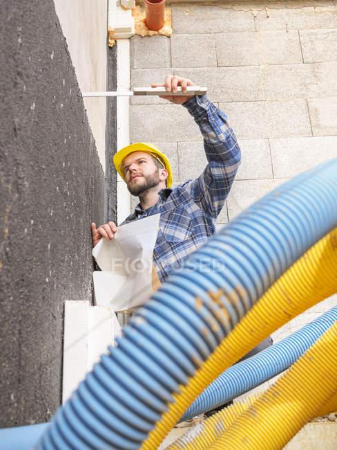 Caposquadra con regola di costruzione piano e tasca controllando i lavori di costruzione — Foto stock