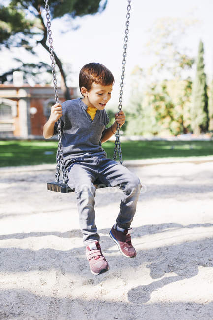 Boy sitting on a swing at the playground — Stock Photo