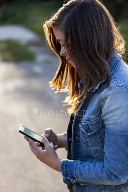 Teenager-Mädchen schaut aufs Smartphone — Stockfoto