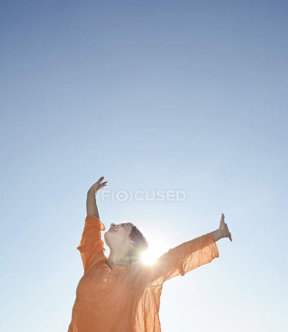 Happy young woman against the sun — Stock Photo