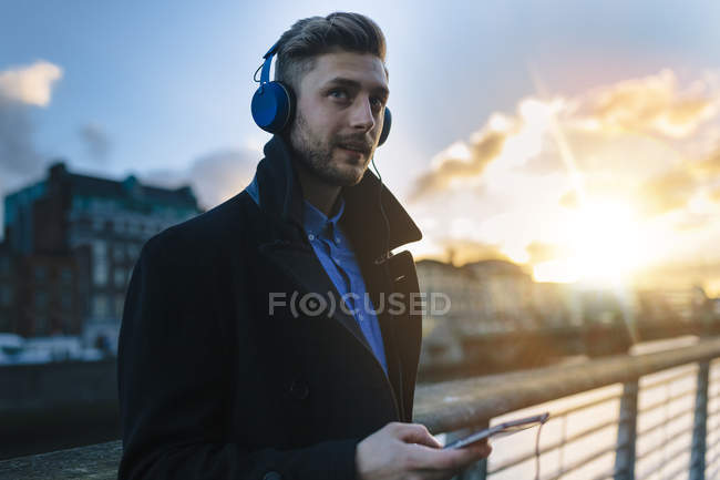 Ireland, Dublin, young man hearing music with headphones at twilight — Stock Photo