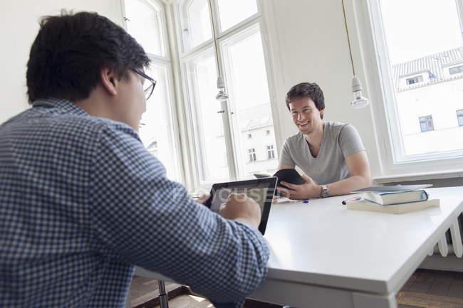 Dois empresários criativos que têm uma reunião em um escritório moderno — Fotografia de Stock