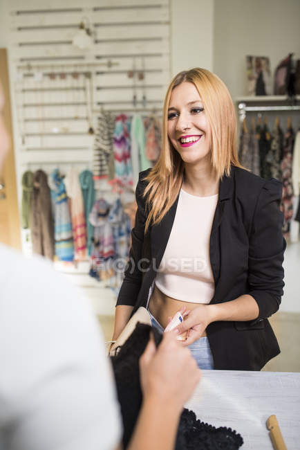 Young woman in fashion boutique paying for purchase — Stock Photo