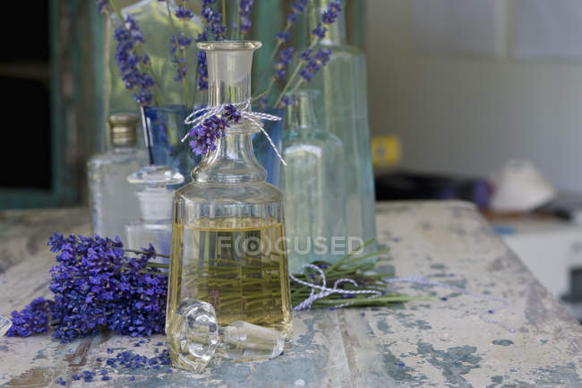 Lavender oil in bottle with flowers and empty glass bottles — Stock Photo