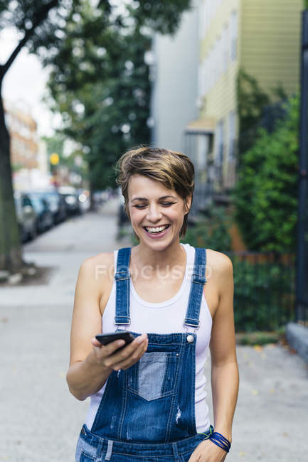 Happy blond woman wearing jeans dungarees with smartphone — Stock Photo