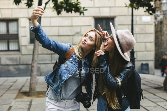Two playful young women taking a selfie in city — Stock Photo