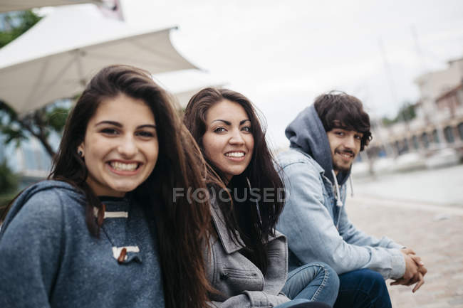 Portrait of three happy friends outdoors sitting at beach — Stock Photo
