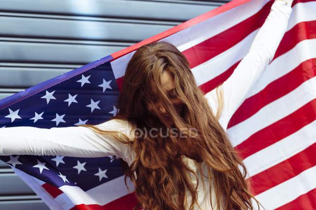 Жінки, що тримає американський прапор з упевненістю — стокове фото