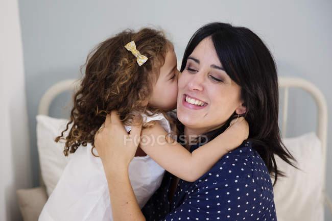 Hija madre de besos en la mejilla en el hogar - foto de stock