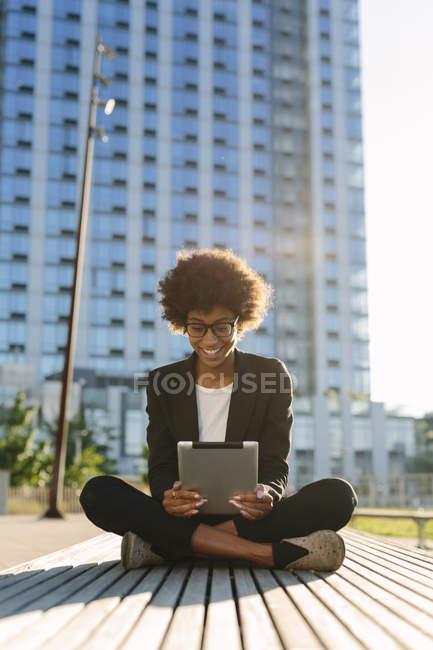 Donna d'affari sorridente seduta su una panchina con tablet digitale — Foto stock