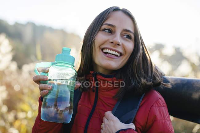 Retrato de mujer feliz excursionista sosteniendo botella de agua - foto de stock