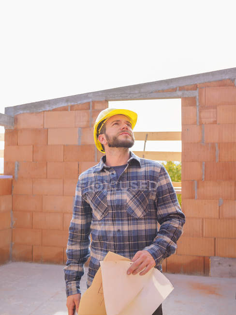 Portrait of foreman with construction plan checking work at construction site — Stock Photo