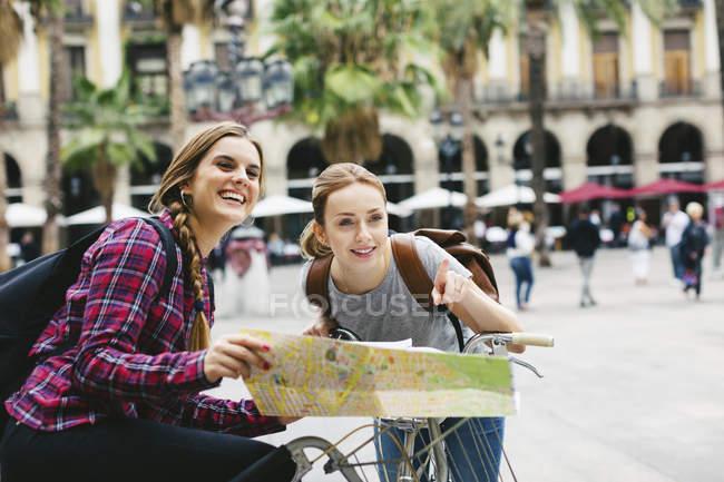 Due giovani donne con mappa sulle biciclette in città — Foto stock