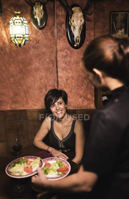 Служачи салат в пластин у ресторані офіціанткою — стокове фото