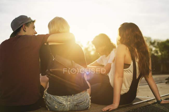 Amigos sentados al aire libre al atardecer - foto de stock