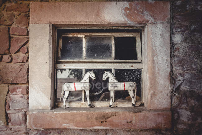 Two vintage toy horses in an old barn on a window sill — Stock Photo