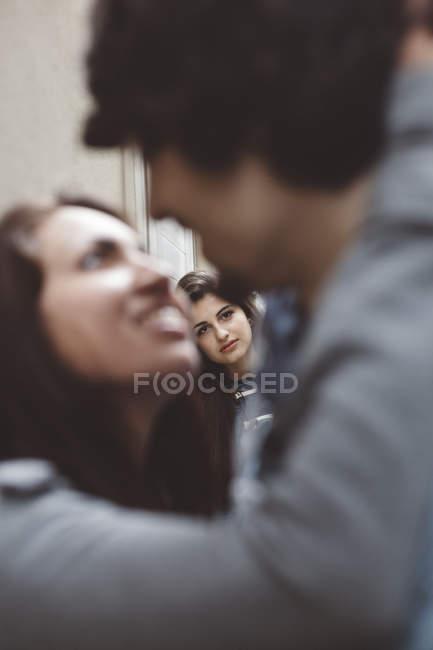 Молодая пара поцелуи с другой женщиной, глядя на них — стоковое фото