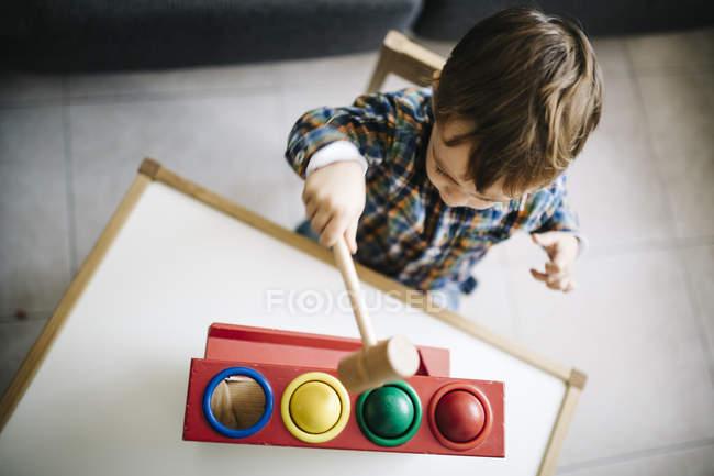 Garçon jouant avec le jouet d'habileté moteur en bois — Photo de stock