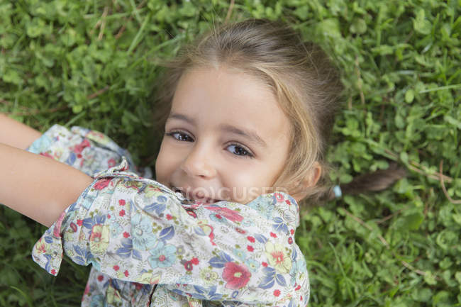 Portrait of smiling little girl lying on a meadow — Stock Photo