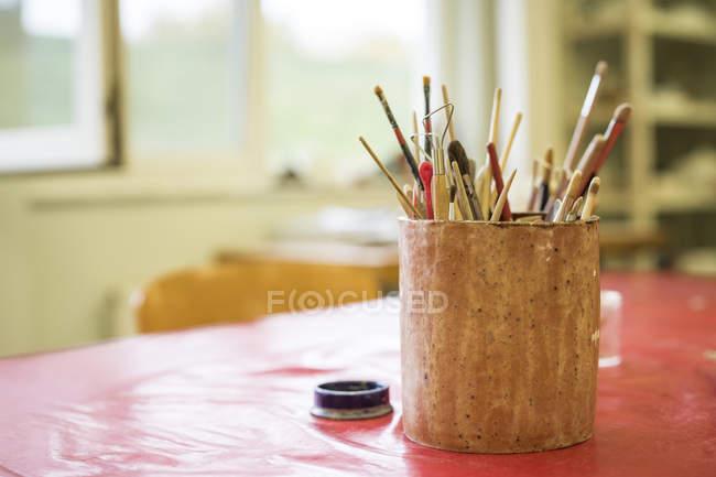 Tasse avec pinceaux et outils sur la table — Photo de stock