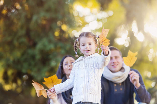 Smiling girl with family holding autumn leaf — Stock Photo