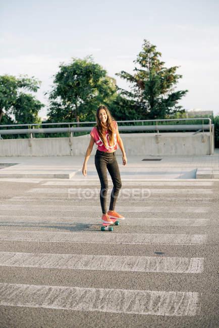 Portrait of smiling skate boarder on zebra crossing — Stock Photo