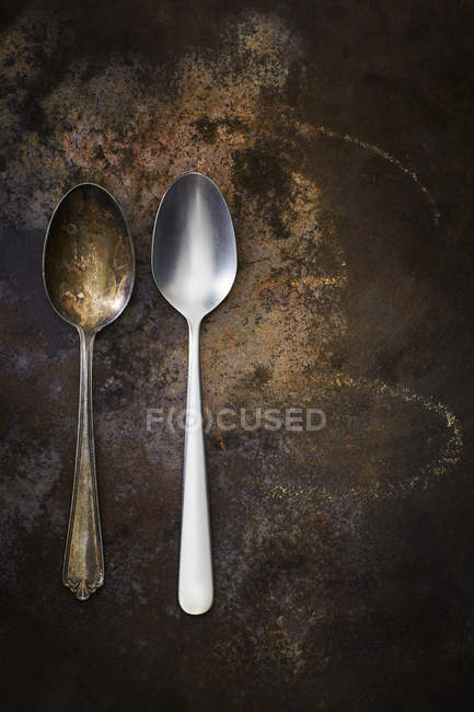 Old and modern spoon side by side on rusty ground — Stock Photo