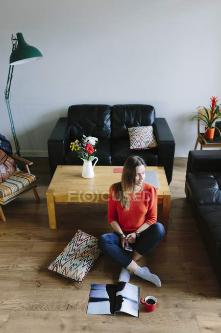 Jeune femme assise sur le sol de son salon relaxant — Photo de stock