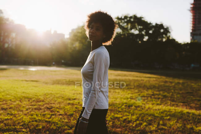 Young woman standing on a meadow of a park at backlight — Stock Photo