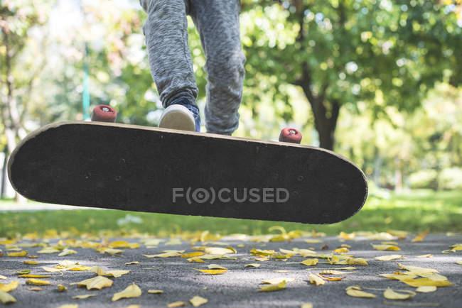 Recadrée vue du garçon faire truc avec skateboard parc automnal — Photo de stock