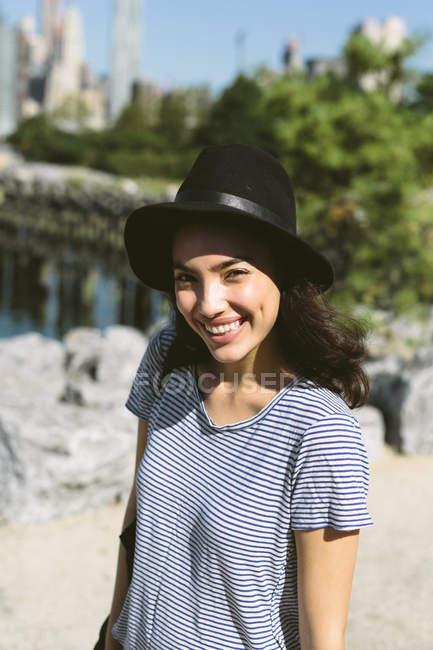 США, Нью-Йорк, портрет улыбающейся молодой женщины в черной шляпе — стоковое фото