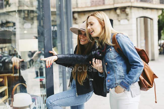 Две молодые женщины смотрят в витрину магазина — стоковое фото