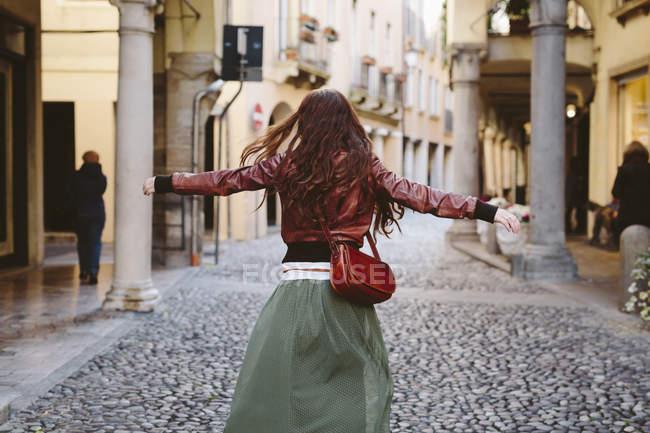 Italien, Padua, Frau zu Fuß mit ausgestreckten Armen in einer Gasse — Stockfoto