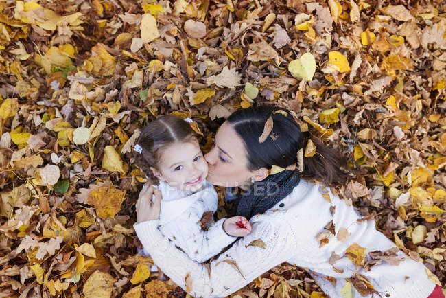 Mãe beijando filha em folhas de outono — Fotografia de Stock