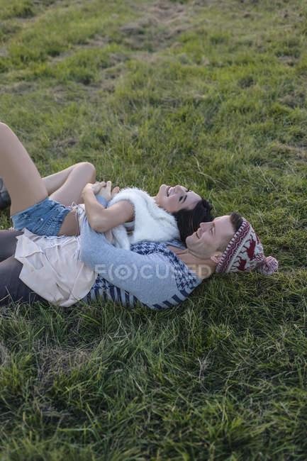 Glückliches verliebtes Paar auf einer Wiese liegend — Stockfoto