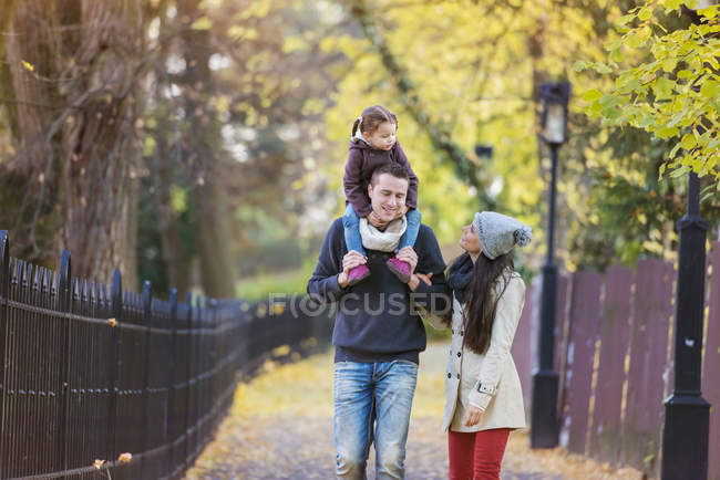 Family going for a walk in autumnal park — Stock Photo