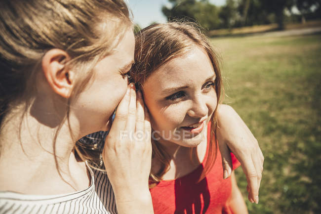 Two teenage girls whispering in park — Stock Photo