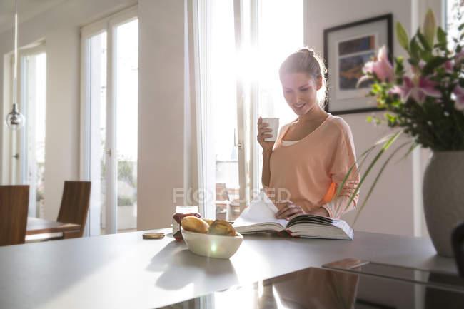 Молодая женщина на кухне завтракает на кухне, читает книги — стоковое фото