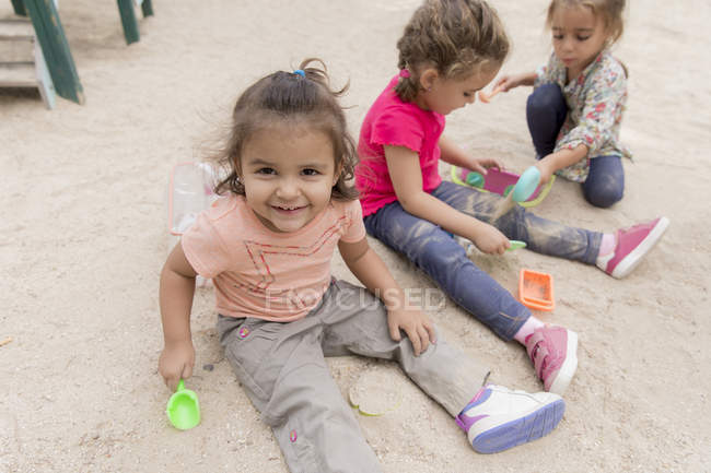 Three little girls playing in sandbox of a playground — Stock Photo