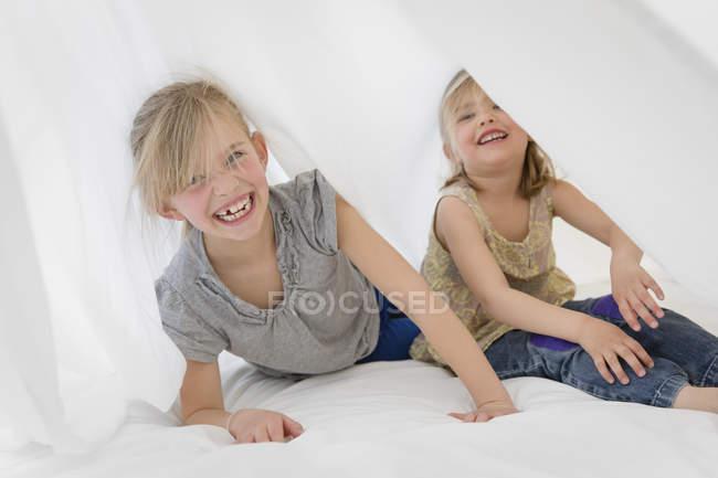 Duas irmãzinhas rindo escondido debaixo de um lençol branco na cama — Fotografia de Stock