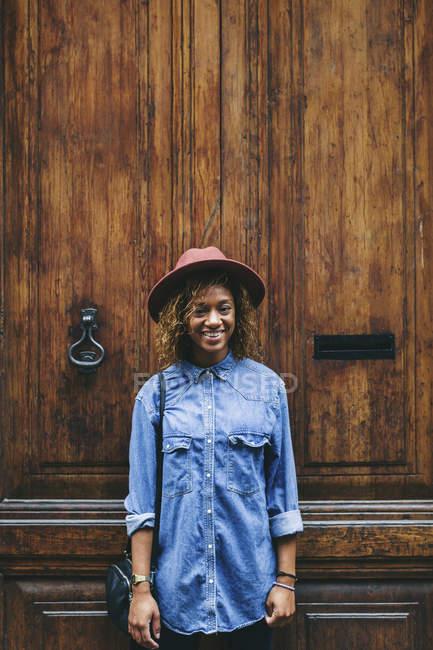 Mulher em frente a porta de madeira — Fotografia de Stock