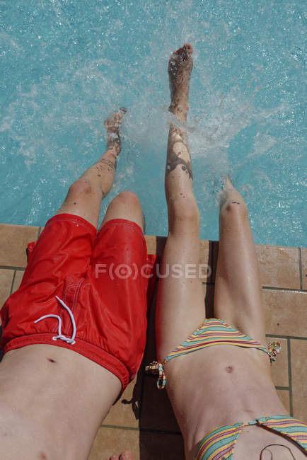 Boy and girl sitting at edge of a swimming pool and splashing water — Stock Photo